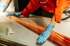 Cukierku producent stacza się handmade pomarańcze i bielu lampasa cukierek rękami z rękawiczkami w Shiroi Koibito parku przy Sapp Obrazy Stock