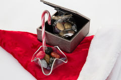 Cukierku trzciny, cukierki i czekolada na Santa kapeluszu odizolowywającym, Fotografia Royalty Free