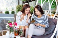Cukiernianego zakup dziewczyn pastylki dwa młodych kobiet online interneta lata kwiatów cyfrowy biały koktajl szczęśliwy dreen li Zdjęcia Stock