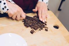 Cukierniany pracownik ciie czekoladę w małych kawałki Zdjęcia Stock