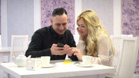cukierniany target630_0_ pary Dobiera się mężczyzna i kobiety opowiada w ślicznych kawiarniach i ogląda na telefonie komórkowym zdjęcie wideo