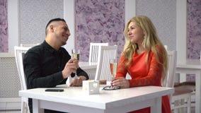 cukierniany target630_0_ pary Dobiera się mężczyzna i kobiety opowiada w ślicznych kawiarniach i ogląda na telefonie komórkowym zbiory wideo