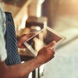 Cukierniany właściciel trzyma cyfrową pastylkę w rękach fotografia royalty free