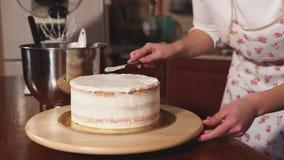 Cukiernicza kobieta zrównuje ostrzem wierzchołek tort z batożącą śmietanką zbiory wideo