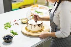 Cukierniczka gniesie ciek?? czekolad? od ciasto torby na bia?ym kremowym ciastko torcie na drewnianym stojaku _ zdjęcia stock