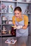 Cukierniczka jest ubranym białe rękawiczki robi fotografii arcydzieło zdjęcie royalty free