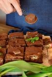 Cukierniczy jest ubranym marynarki wojennej błękita fartuch zakrywa torty z cacao proszkiem zdjęcie stock