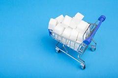 Cukrowi sze?ciany Góra cukier w wózku na zakupy na błękitnym tle Odg?rny widok zdjęcia royalty free