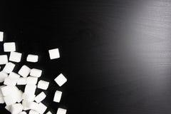 Cukrowi sześciany na czarnym tle Zdjęcia Stock