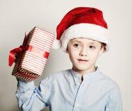 ¿Cuál está en la caja de la Navidad? Niño con el regalo de la Navidad Imagenes de archivo
