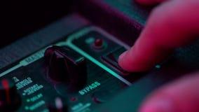Culbuteur de commutateur électrique tourné en marche et en arrêt par le musicien Lampe au néon colorée Fermez-vous vers le haut d clips vidéos