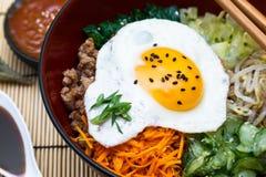 Culinária coreana, Bibimbap da carne em um potenciômetro de argila sobre foto de stock