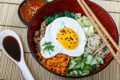 Culinária coreana, Bibimbap da carne na bacia vermelha fotografia de stock