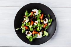 Culinária italiana Salada caprese italiana fresca com mussarela e tomates na placa escura na tabela de madeira branca Vista super Foto de Stock