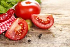 Culinária italiana: tomates, azeitonas e folhas da manjericão na aba de madeira Foto de Stock Royalty Free