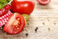 Culinária italiana: tomates, azeitonas e folhas da manjericão na aba de madeira Fotografia de Stock