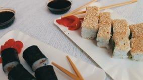 Culinária japonesa do sushi-maki com salmões, o gengibre cor-de-rosa, wasabi verde e molho de soja nas placas brancas vídeos de arquivo