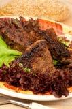 Culinária nacional grega - fatias fritadas de um fígado Fotografia de Stock
