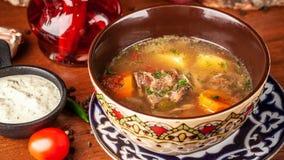 Culinária oriental do Uzbeque tradicional Sopa com carne do cordeiro Copie o sp imagens de stock