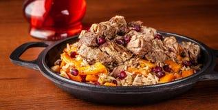 Culinária oriental, pilau ou plov do Uzbeque tradicional com grande torta foto de stock