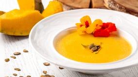 Culinária ucraniana Sopa do puré da abóbora, com creme, sementes de abóbora e flores em uma placa branca imagens de stock