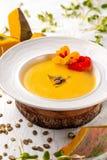 Culinária ucraniana Sopa do puré da abóbora, com creme, sementes de abóbora e flores em uma placa branca fotografia de stock