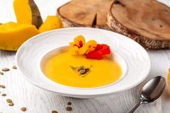 Culinária ucraniana Sopa do puré da abóbora, com creme, sementes de abóbora e flores em uma placa branca imagens de stock royalty free