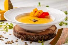 Culinária ucraniana Sopa do puré da abóbora, com creme, sementes de abóbora e flores em uma placa branca fotos de stock
