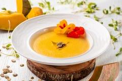 Culinária ucraniana Sopa do puré da abóbora, com creme, sementes de abóbora e flores em uma placa branca fotos de stock royalty free