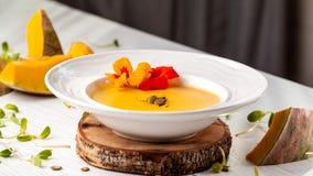 Culinária ucraniana Sopa do puré da abóbora, com creme, sementes de abóbora e flores em uma placa branca imagem de stock