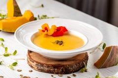 Culinária ucraniana Sopa do puré da abóbora, com creme, sementes de abóbora e flores em uma placa branca foto de stock royalty free