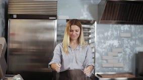 Culinario, concepto de los pasteles Retrato de un confitero rubio de la mujer que se coloca antes de tabla de funcionamiento y qu almacen de metraje de vídeo