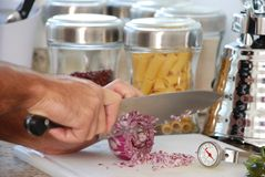 Culinary. Chef cutting the onions on board Royalty Free Stock Images