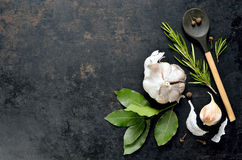 Culinary background. Dark culinary background with a wooden spoon along with garlic, rosemary, bay leaves, pepper and some cloves pictured on it royalty free stock images