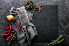Culinary background with empty black slate board. Dark culinary background with empty black slate board and space for text recipe or meat menu Stock Image