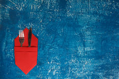 Culinary background. Fork and knife folded in a napkin on a blue Stock Photography