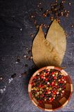 Culinary background with laurel leaves and spices on a dark concrete background. Close-up of a culinary background with two bay leaves, spilled spices, and Stock Photo