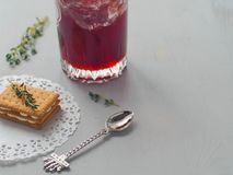 Culinary background. Layered cookie decorated with fresh thyme sprigs and a glass of strawberry jam half full with funny spoon. royalty free stock images