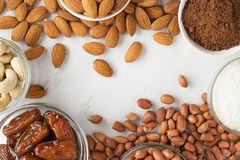 Culinary background with nuts, dates, coconut flakes and cocoa powder on white wooden table. royalty free stock photos