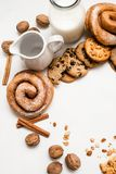 Culinary background of pastry food. Top view free space. Wholegrain scones and baked rolls with walnuts and cinnamon laying near bottle and pitcher of milk Stock Photos