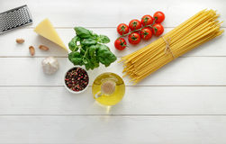 Culinary background with raw ingredients for pasta recipe on white wooden background. Dry bucatini or spaghetti with fresh tomatoes, basil and cheese. Top view Royalty Free Stock Photos