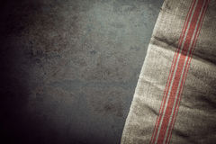 Culinary background of a rustic cloth on slate. Culinary background of a rustic textured cloth on slate with copyspace and vignetting for your menu, recipe or Stock Images
