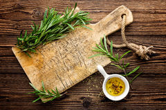 Culinary background with wooden board and cooking ingredients, olive oil and rosemary, above view, space for a text Stock Images