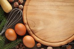 Culinary baking background with cutting board, eggs, whisk, nuts. royalty free stock image