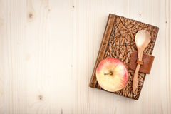 Culinary concept background. Of apple and notebook on wooden table Royalty Free Stock Images