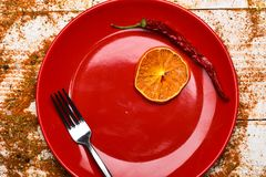 Culinary concept. Plate and fork with dried orange and chilly pepper on white wooden background. Spices scattered all. Over wooden surface. Spices as grinded stock photo