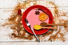 Culinary concept. Spices as grinded red pepper and curcuma powder scattered. Spices scattered all over wooden surface. Plate and fork with dried orange and stock photos