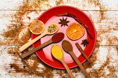 Culinary concept. Spices scattered all over wooden surface. Plate and spoons with dried orange and chilly pepper on. White wooden background. Spices as grinded royalty free stock photos