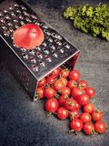 Preparation recipe tomato juice. Large tomato and old grater down to small grape cherry tomatoes on retro vintage rustic gray ston Stock Photo