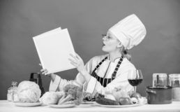 Culinary expert. Woman chef cooking healthy food. Girl read book top best culinary recipes. Culinary school concept. Female in hat and apron knows everything stock image